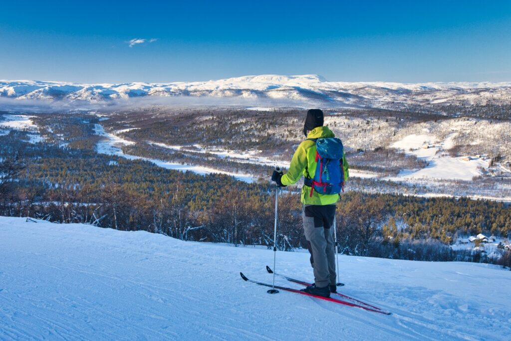 Cross-country skiing at Dagalifjell near Geilo, Uvdal, Hardangervidda is widely practiced as a sport and recreational aktivity. A man standing and looking at Numedalslågen.